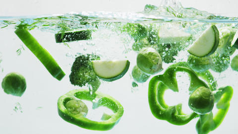 Green Vegetable Slices Falling into Water Footage