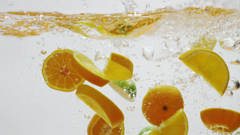 Oranges and Limes Slices Falling into Water Footage