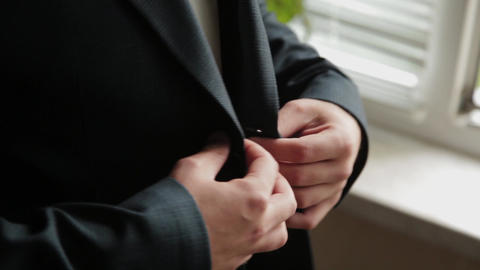 Stylish male businessman straightens his jacket Live Action