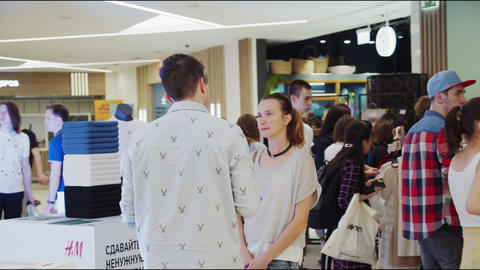 volunteer talks with woman at charity event in shopping mall Live Action