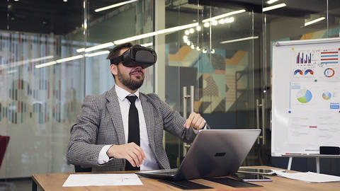 Front view of good-looking contented bearded manager in virtual reality headset Live Action