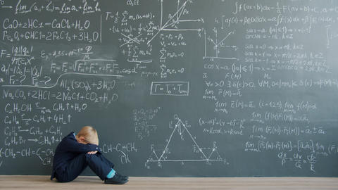 Sad child sitting on floor near chalkboard wall thinking solving problem alone Live Action