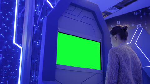Green screen concept - woman looking at blank green display kiosk at exhibition Live Action
