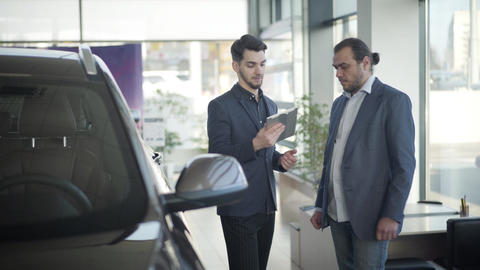 Young Caucasian car dealer giving tablet to successful rich customer in showroom Live Action