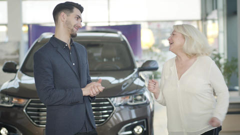Young positive Caucasian car dealer giving keys to mature cheerful woman in Live Action