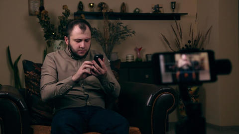 Shocked men reading message via smartphone while recording video on the phone Live Action