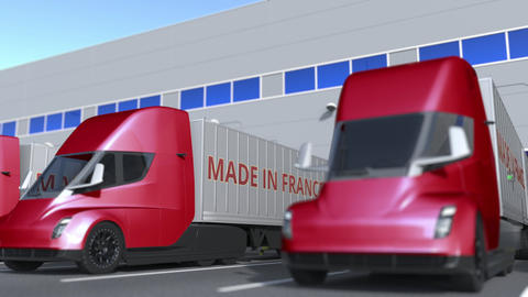 Modern semi-trailer trucks with MADE IN FRANCE text being loaded or unloaded at Acción en vivo