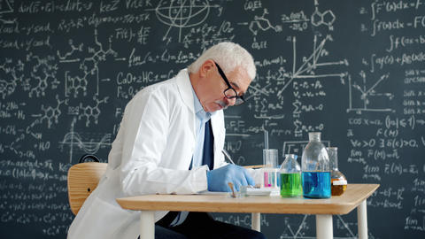 University professor writing in class at desk with chemical equipment glass Live Action