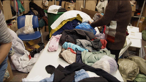 women check second hand clothes on table in storage closeup Acción en vivo
