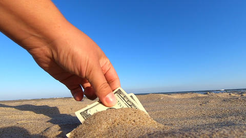 A girl takes out from the sand money notes of three hundred dollars Acción en vivo