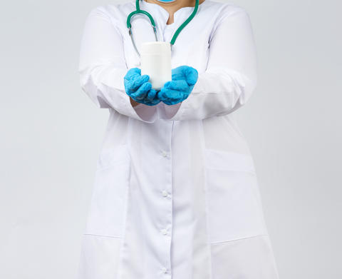 a female doctor in a white coat and mask holds a white plastic j Fotografía