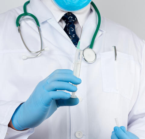 male doctor in a white coat and tie stands and holds a plastic s Fotografía