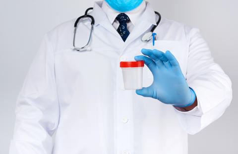 male doctor in a white coat and tie stands and holds a plastic c Fotografía