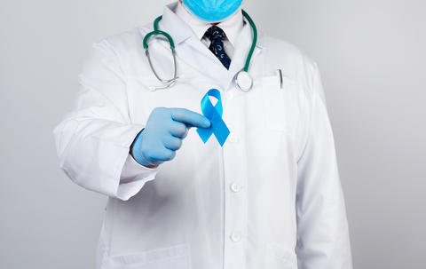 male doctor in a white coat and tie stands and holds a blue silk Fotografía