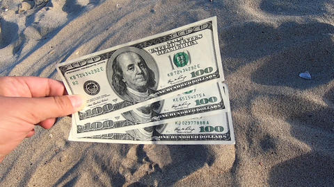 Girl holding money bill of 300 dollars on background of over sand Acción en vivo