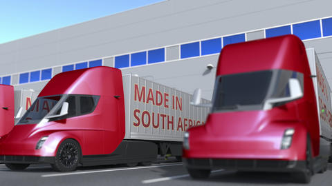 Modern semi-trailer trucks with MADE IN SOUTH AFRICA text being loaded or Acción en vivo