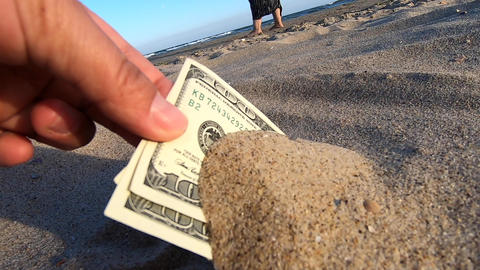 A girl takes out from the sand money notes of three hundred Acción en vivo