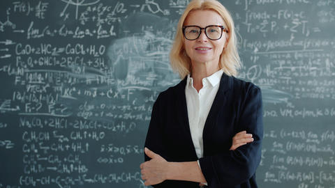 Portrait of friendly lady teacher standing in classroom with arms crossed alone Live Action