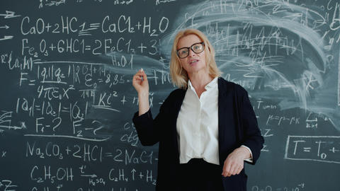 Slow motion of adult woman teaching science at class near chalkboard talking Live Action