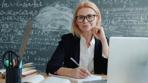 Friendly mature lady smiling sitting at desk in classroom looking at camera Live Action