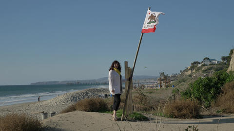 Woman happy Beautiful sunny summer holding california republic flag ocean coast Live Action