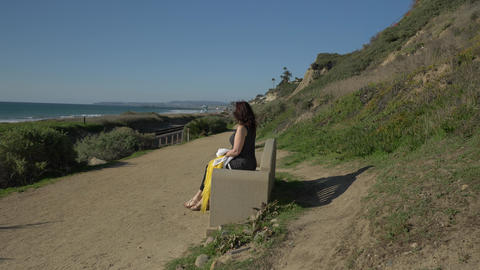 Woman happy Beautiful sunny summer Day sitting on the bench side view at ocean Live Action