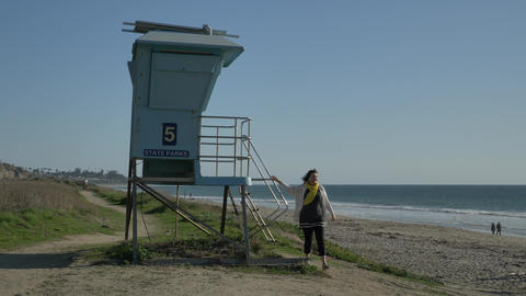Woman walking from lifeguard tower and waving at summer day . Travel Vacation Live Action