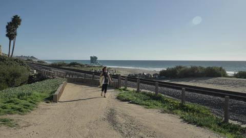 Woman happy Beautiful sunny summer Day Walking at ocean coast close to rails Live Action