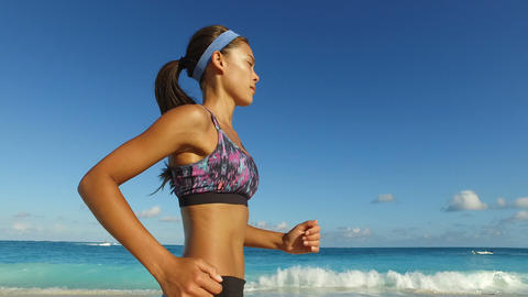 Determined Woman Jogging On Beach Against Blue Sky - Healthy Active Lifestyle Live Action