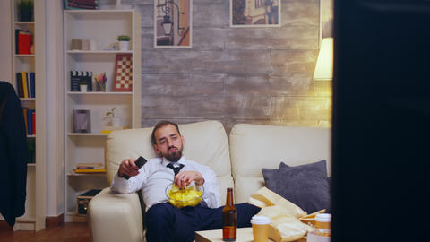Tired and bored businessman with tie relaxing watching tv Live Action