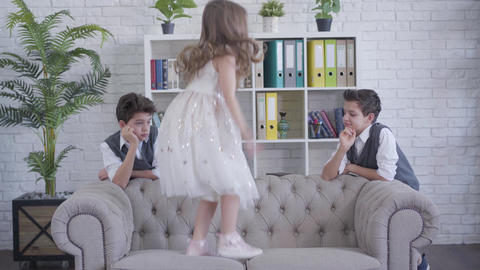 Little cheerful Caucasian girl jumping on couch and stretching boy's hand Live Action