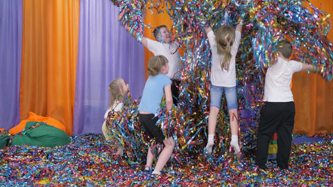 Colored ribbons fly in different directions. Children have fun. Bright children Live Action