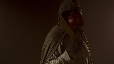 Killer in monster mask and cloak hoodie gestures cut throat with knife Live Action