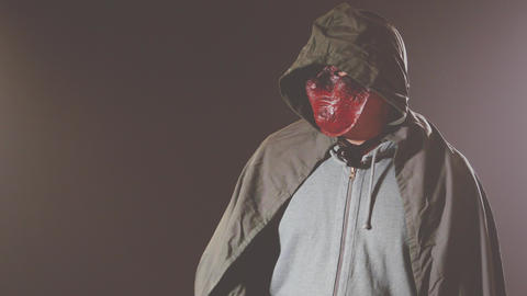 Killer in monster mask and cloak hoodie swings knife Live Action