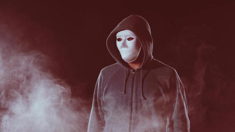 Killer in white mask and hoodie looks around Live Action