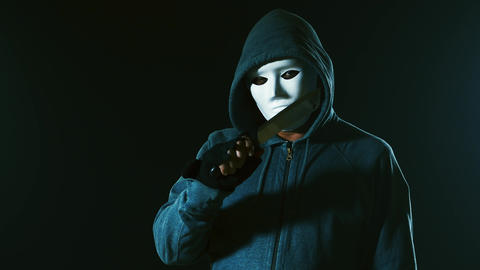 Killer in white mask and hoodie shows knife walks past camera Live Action