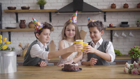 Cheerful girl and two identical boys clinking cups and drinking tea at birthday Live Action