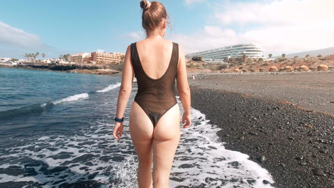 4k toned video of sexy young woman in transparent swimsuit walking and relaxing Live Action