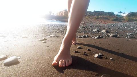 Closeup 4k video of beautiful female feet walking on volcanic black sand on Live Action