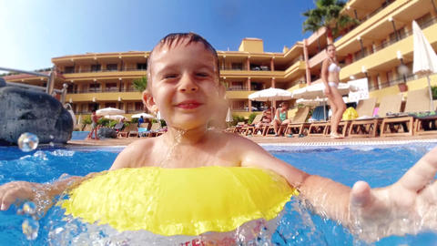 Slow motion video of cheerful little boy with inflatable ring splashing water Live Action
