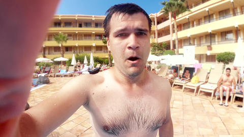 Slow motion video of young man jumping in outdoor swimming pool at summer hotel Live Action