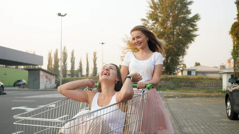 4k video of happy laughing girls having fun while riding in shopping on parking Live Action