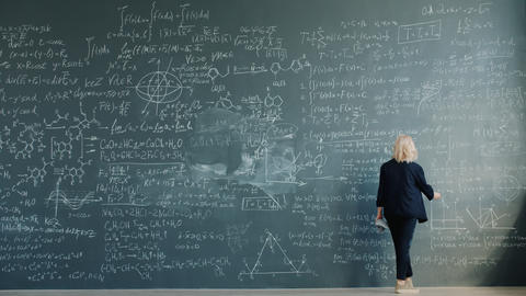 Time-lapse of female scientist writing formulas on chalkboard working alone Live Action