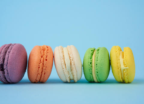 multi-colored round baked macarons cakes on a light blue backgro Fotografía