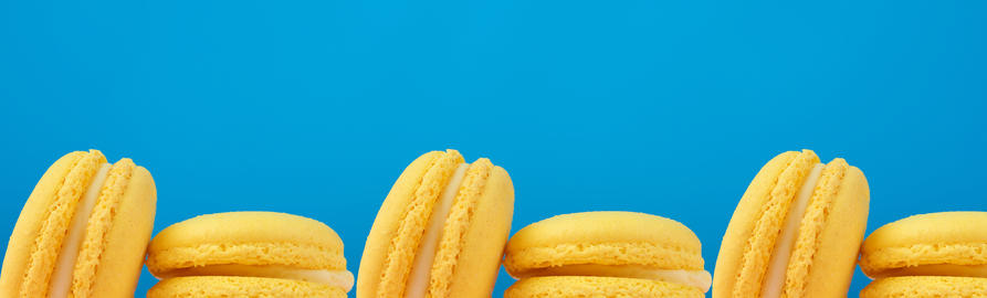 halves of baked round yellow lemon macaron on a blue background Fotografía