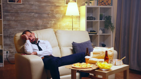 Overworked businessman sleeping on the couch Live Action