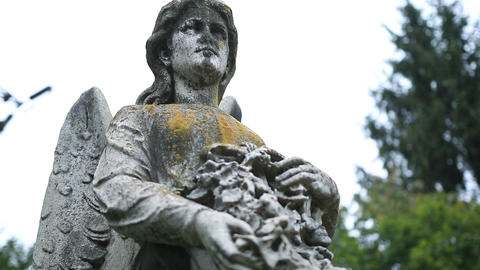 Closeup statue of angel holding wreath at cemetery Footage