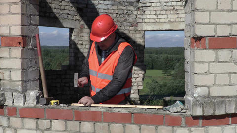 Builder with hammer drives the nail in to timber Live Action