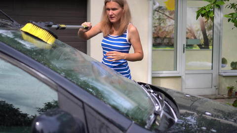 Wife brushing husband car windscreen with long brush shampoo foam in house yard Live Action