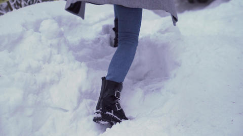 Young girl walking in deep snow outdoors during holidays Live Action